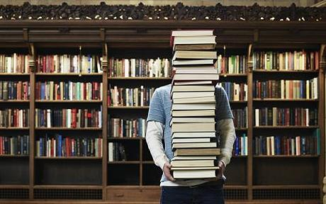 person hidden by stack of books